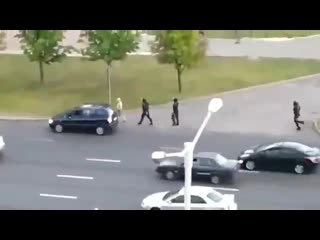 ОМОНовец стоит и бьёт проезжающие машины