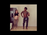 Pregnant couple dance with their baby