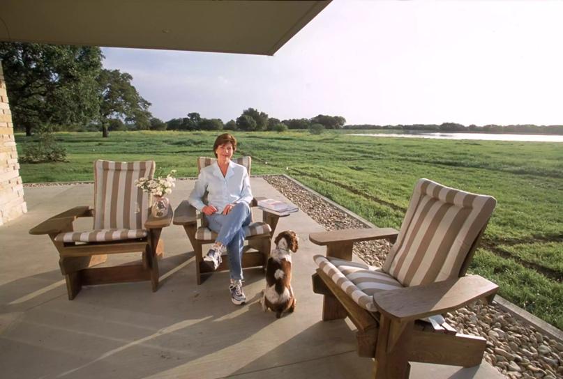 Первая леди Лаура Буш, жена президента Джорджа Буша, во внутреннем дворике их дома в Кроуфорде, штат Техас. Рик Уилкинг / Архив Халтона / Getty Images
