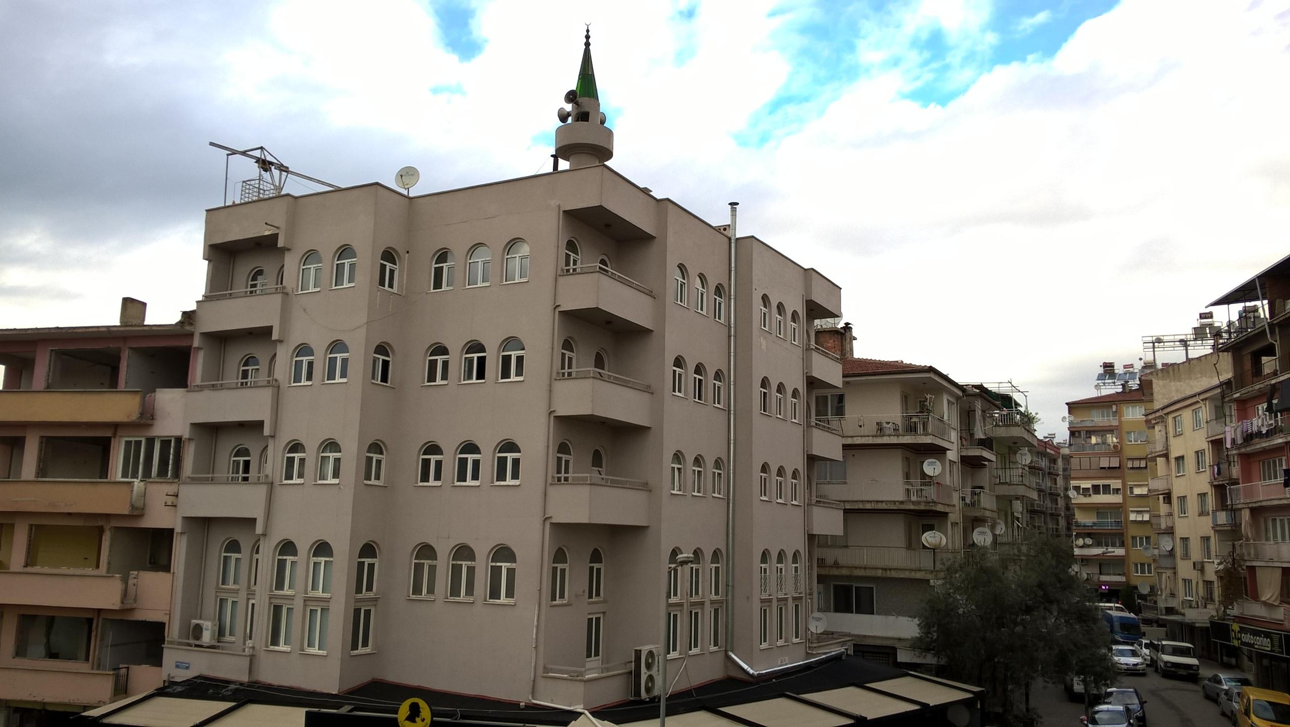 Минарет мечети присоединён к крыше жилого дома